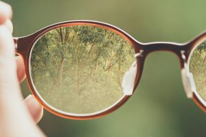 person holding brown eyeglasses looking out at trees