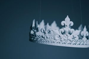 white crown suspended by thin wires
