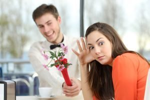 Woman rejecting man's offer of flowers