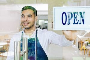 Young, happy man behind glass door of business, changing to Open sign