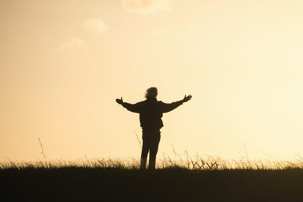 silhouette of person with open arms